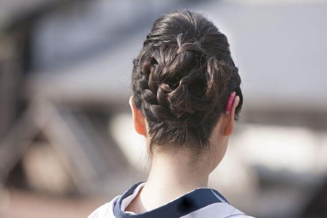 黒い着物にピンク色の羽織を合わせ髪をすっきりまとめたうなじ美人の後ろ姿