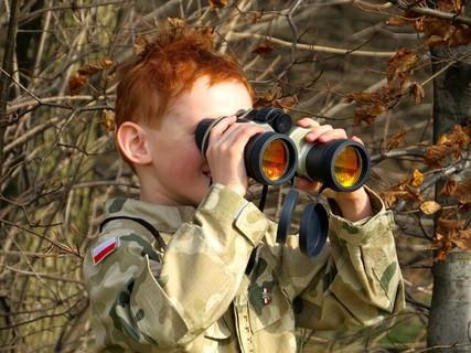 双眼鏡を覗いて何が必要なのか発見する軍服を着た男の子