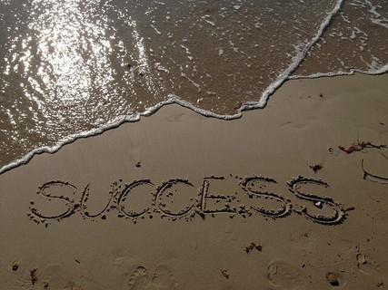 目標達成の気持ちをこめて砂浜に書かれた「success」の文字
