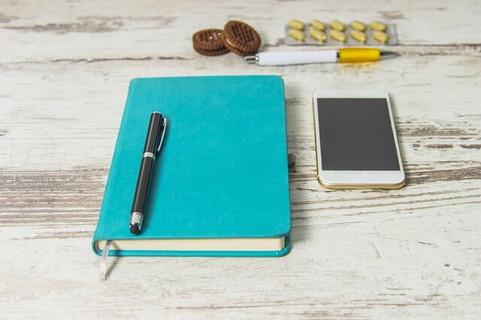 白い机の上に置かれた目標を書き込まれた手帳