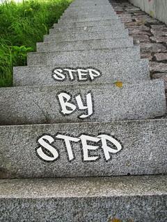 「step by step」とかかれた成功へと続く長い階段