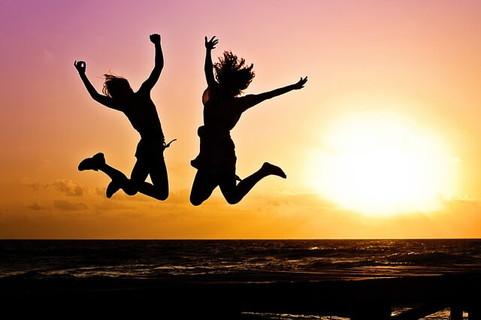 海に沈む夕日を背にジャンプするダイエットしてキレイなボディを手に入れてた女の子2人