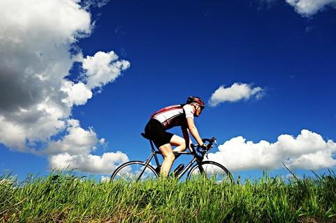 青空の中をマウンテンバイクで気持ち良さそうに走る男性
