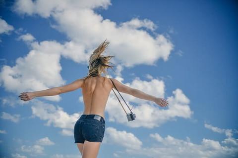 青空の下、カットオフデニムをはきトップレスで歩くスタイルに自信がある女の子の後ろ姿