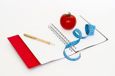 サイズと食べたものを記録する予定の赤い表紙のノートとメジャーとトマト