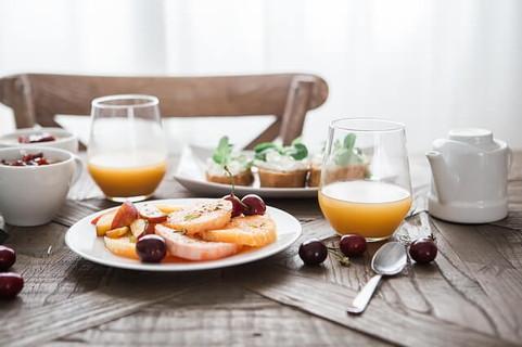 たっぷりのフルーツとオレンジジュースとオープンサンドの見た目にも美しくバランスの取れた朝ご飯