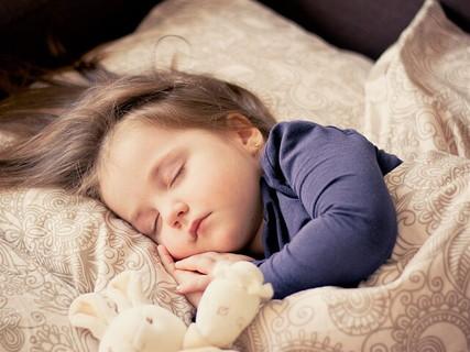 ベッドに入り気持ち良さそうにグッスリ眠る女の子