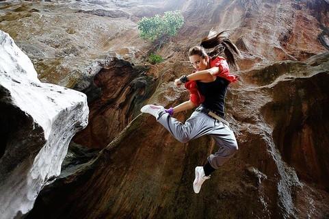 大自然の中でジャンプし戦闘態勢を取る日々格闘技を続けている女性