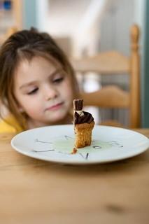 お皿に乗った半分に切られたカップケーキを食べようかどうか悩んでいる女の子