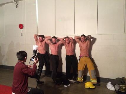 上半身裸ですばらしい肉体を見せる男性4人とそれを写真に収めるカメラマン