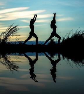 湖のほとりで朝日が昇る中ヨガをする健康的な女性2人