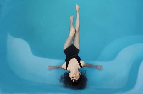 プールサイドに頭を乗せ水に身をまかせてリラックスする女性