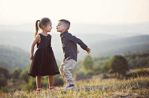 丘の上で女の子にキスをしようと近付く可愛い男の子