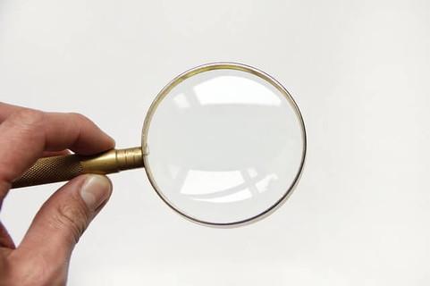 原因を虫眼鏡で探す女性の手