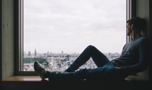 岩に腰を下ろし、海を眺める孤独が好きな男性