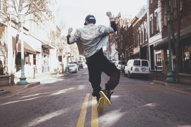 飛び跳ねるいつも明るくフットワークの軽い男性