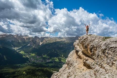 困難な道のりを乗り越えて頂上にたどりつきビクトリーポーズを決める女性