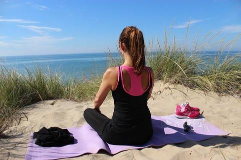 海辺にヨガマットをしき、今この瞬間に集中して瞑想をする女性