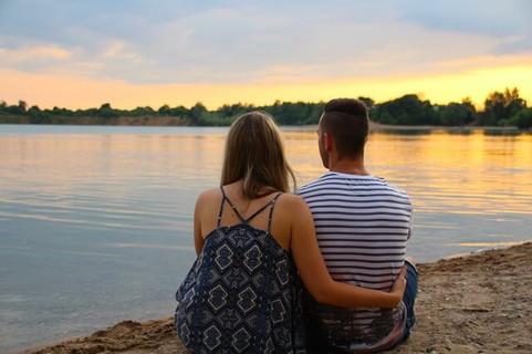 夕日を眺めながら桟橋に座り身を寄せ合うカップル