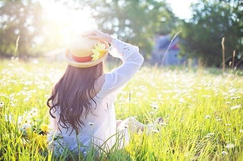 花が咲く草むらに腰を下ろして太陽を見上げる女性