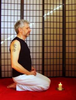 腕に覚悟の文字を刻み、正座し瞑想にふける男性