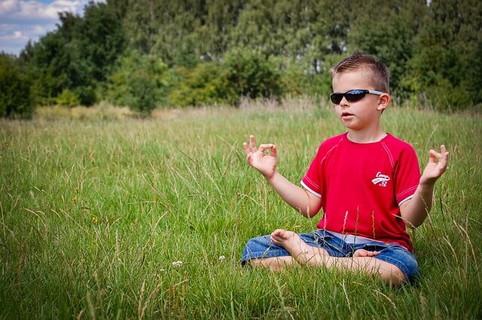青々と茂った草むらに座り座禅を組み瞑想をするサングラスをかけた男の子