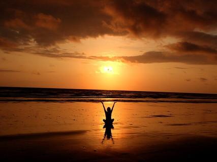 夕日が沈む海を前に気持ち良さそうに手を上げる瞑想をして心がスッキリした女性