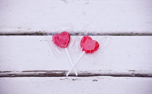 カップルのように白い木のテーブルに並んだ2つの赤いキャンデー