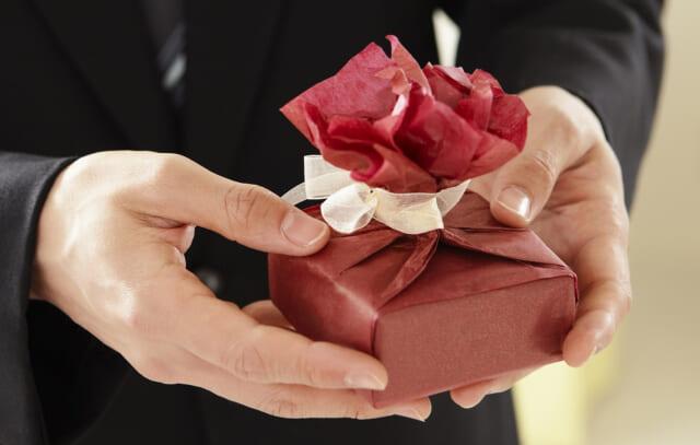 お菓子の入った小さな赤い包みを両手で差し出す男性