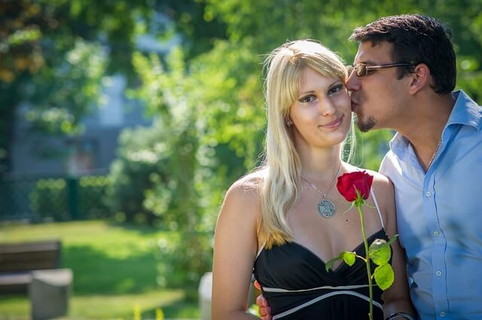 ホワイトデーのお返しに赤いバラとたくさんの気持ちを貰って幸せそうな女性とそのほっぺたにキスをする男性