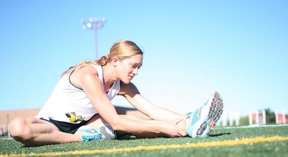 青空の中、健康管理のためのランニングをするために念入りにストレッチする女性