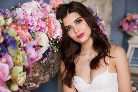 色とりどりの花に囲まれてじっとこちらを見る白いドレスを着た女性