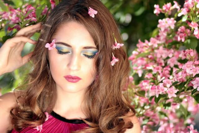 桜の花を背景にドキドキした気持ちを必死に押さえようとする女性