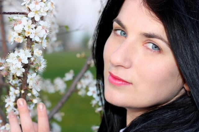 桜の花に顔を寄せてカメラに目線を向ける女性