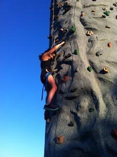 試練のような高い塔をロッククライミングで登る女の子