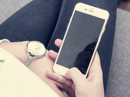 腕時計を眺めながら待ち合わせの時間を過ぎても現れない相手に連絡を入れようか迷っている女性