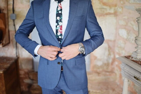 お気に入りのスーツに身を包み身だしなみを確認する男性