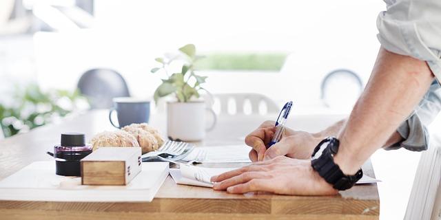 コーヒーを飲みながらデートプランを紙に書き留める男性