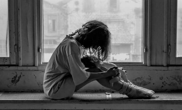 自分のことが嫌いになり絶望的になって窓辺に座りこむ女性
