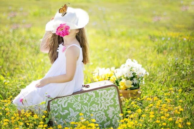 お花畑に座り白い帽子で視界をさまたげながら蝶と戯れる女の子