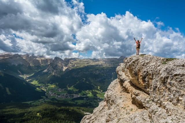ネガティブ思考を何度も何度も乗り越えて頂上にたどり着きビクトリーポーズを決める女性