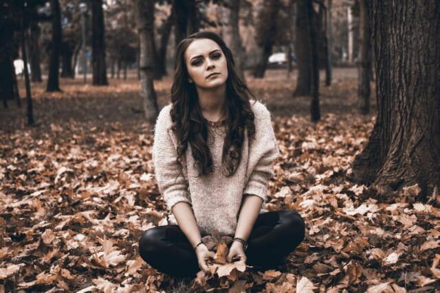 落ち葉の上に腰を下ろし不機嫌そうな顔をしつつも魅力がある女性