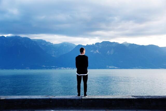 湖の前に立ち自分自身としっかり向き合う時間を作る男性