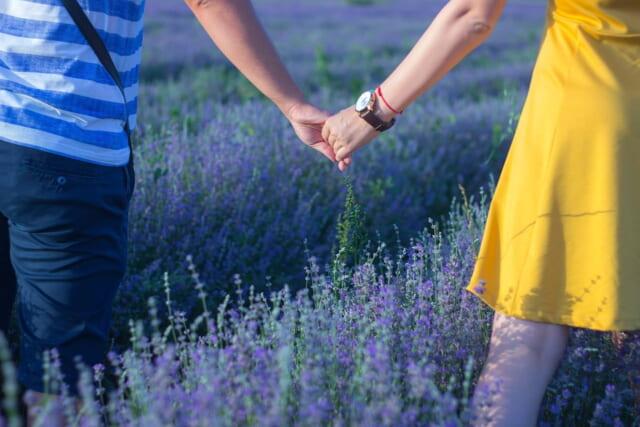 真っ暗な海辺でぼんやりとした灯りに照らされながらキスを交わす幸せそうなカップル