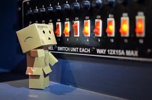 さまざまなスイッチが並ぶ機械の前で全てをリセットしようと手を伸ばすダンボー