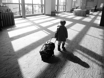 トランクを引いて空港内を歩く旅行慣れしている小さな男の子