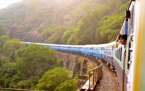 絶景の中を走る長い列車とワクワクしながら外を眺める女性