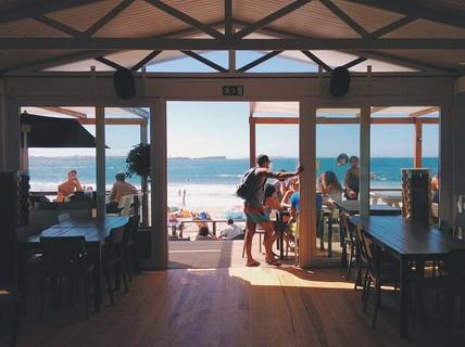 旅行者がたくさん集まる白い砂浜のビーチに立つカフェ