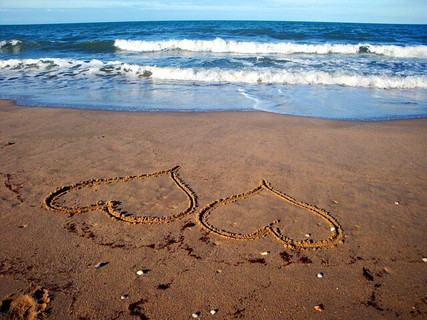 偶然の出会いの象徴のように砂浜に描かれた2つのハート