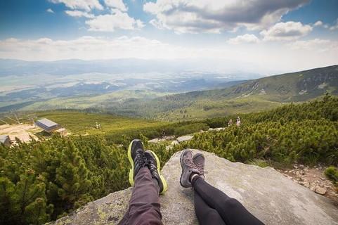 見晴らしの良い丘の上で並んで座るカップル